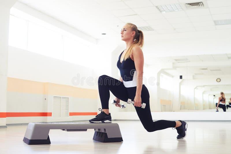 Sobre la opinión la mujer que ejercita aeróbicos del paso con pesas de gimnasia fotografía de archivo libre de regalías