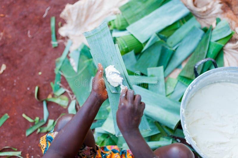 Sobre la opinión la mujer africana da la fabricación traditonal de baton camerunés de manioc con las hojas del manioca y del llan foto de archivo libre de regalías
