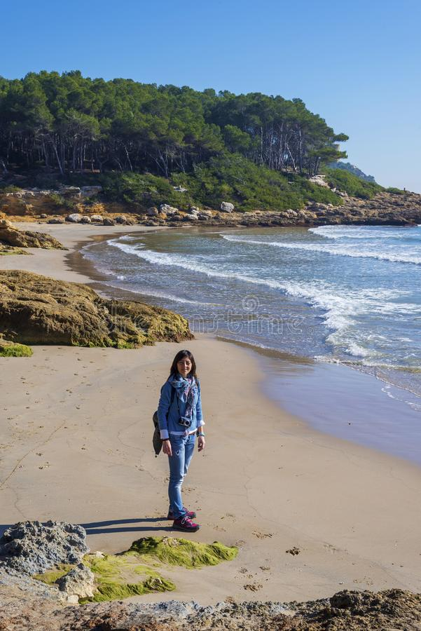 Sobre la opinión una mujer joven que lleva la ropa casual que se coloca en la playa mientras que mira a la cámara en un día brill imagenes de archivo