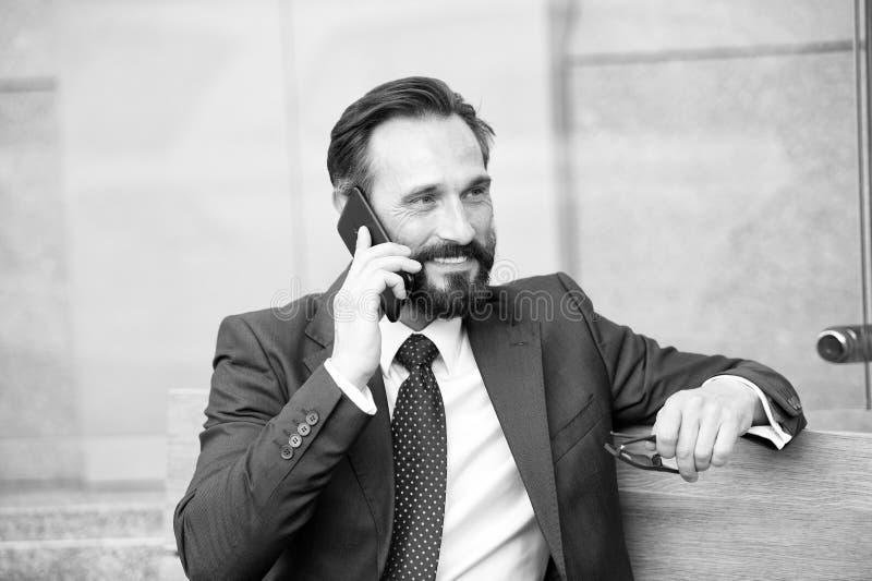 Sobre o telefone Retrato do homem de negócios moderno que fala no Smart-telefone ao sentar-se no banco fora homem farpado que gua fotografia de stock