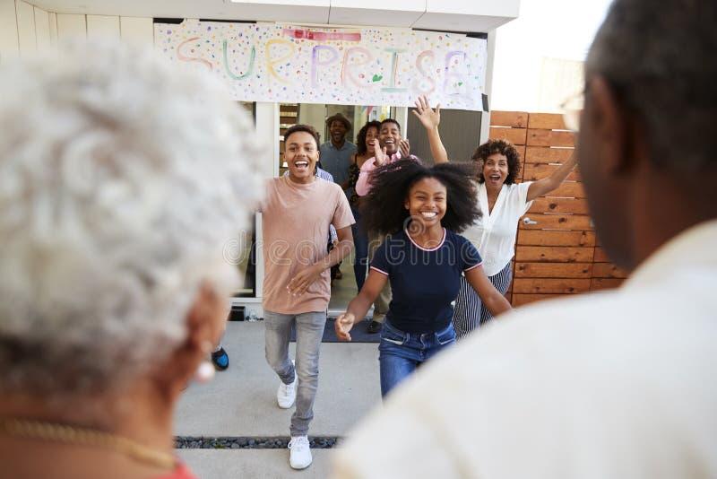 Sobre a opinião do ombro a família que corre para dar boas-vindas a avós para um partido da família da surpresa fotos de stock royalty free