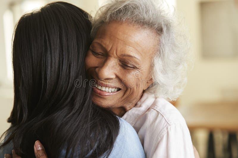Sobre a opinião do ombro a mãe superior que está sendo abraçada pela filha adulta em casa fotografia de stock