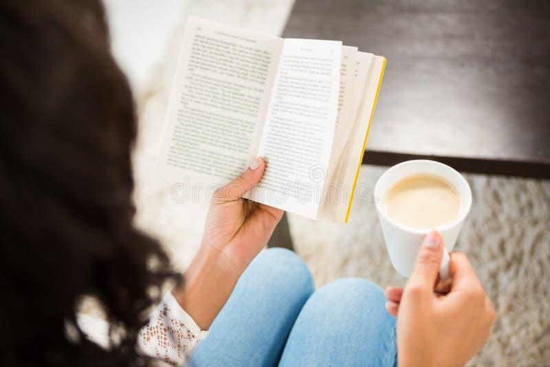 Sobre a opinião do ombro a mulher que guarda a xícara de café e o livro fotografia de stock