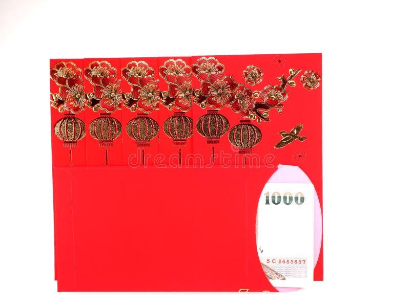 Sobre rojo y dinero tailandés en el fondo blanco fotos de archivo libres de regalías