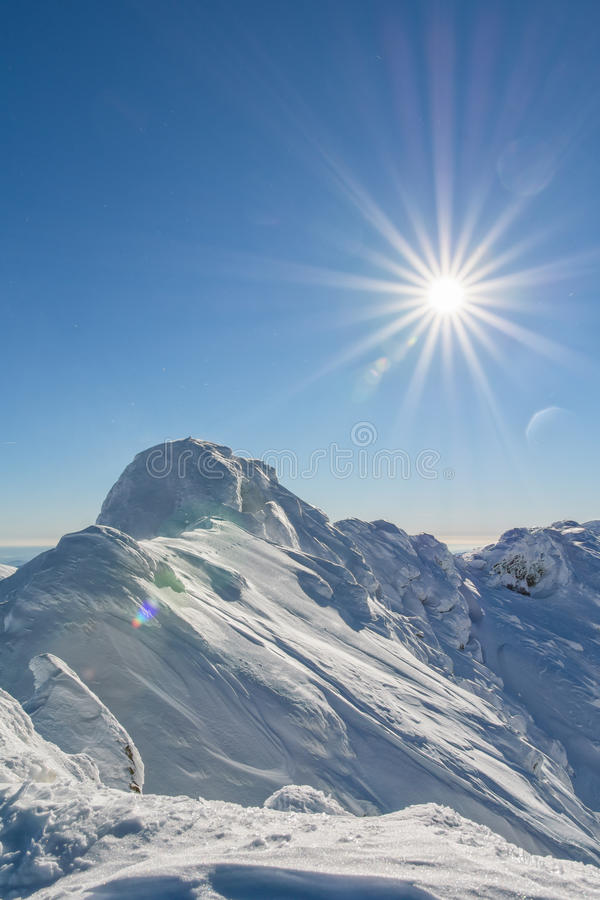 Sobre um pico de montanha nevado imagem de stock