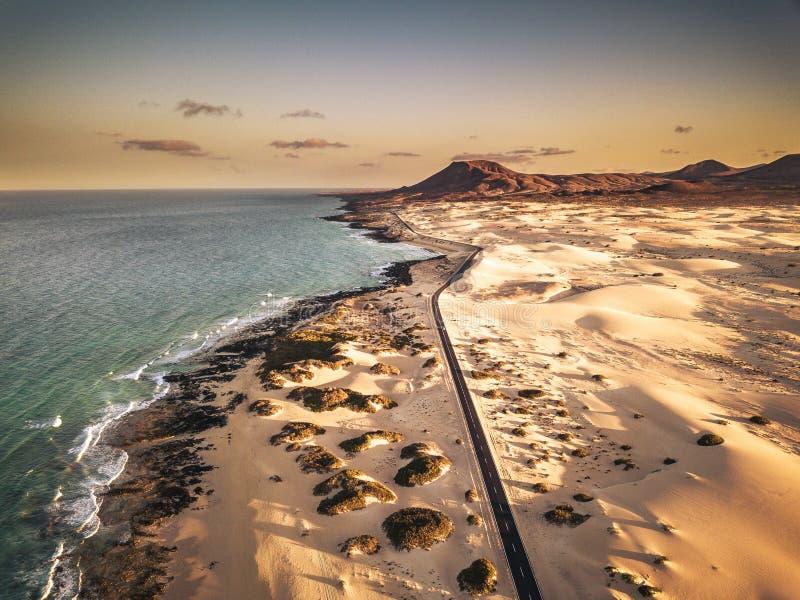 Sobre a vista da praia de areia tropical amarela com estrada e carro de longo curso preto - ondas azuis oceânicas e costa - pôr d foto de stock