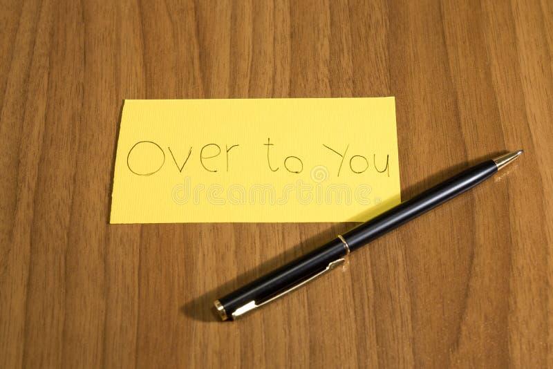 Sobre a você handwrite em um papel amarelo com uma pena em um teble imagens de stock royalty free