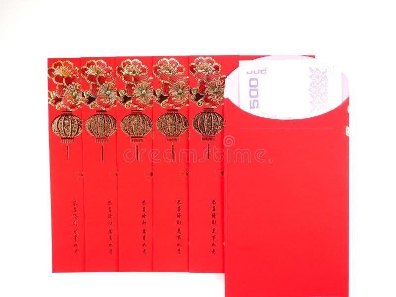 Sobre y dinero rojos en el fondo blanco fotografía de archivo