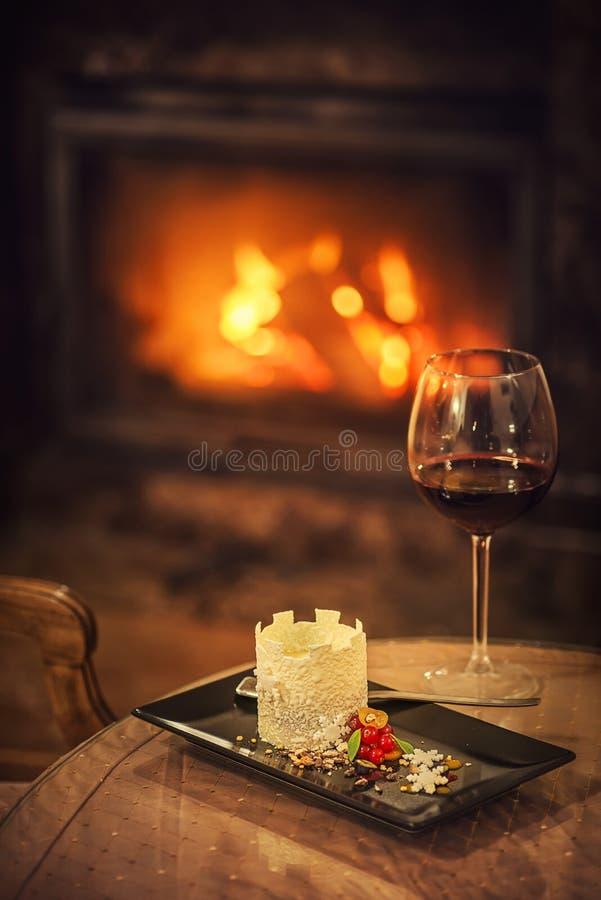 A sobremesa bonita do inverno como o castelo com flocos de neve e frutos serviu na placa branca com vidro do vinho tinto, fotogra fotos de stock royalty free