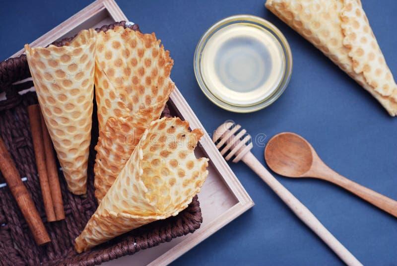 Sobremesa caseiro dos cones vazios do waffle com acessórios e o honney de madeira Fundo para um cartão do convite ou umas felicit imagem de stock royalty free