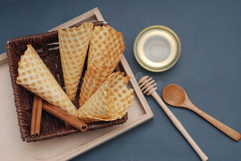 Sobremesa caseiro dos cones vazios do waffle com acessórios e o honney de madeira Fundo para um cartão do convite ou umas felicit fotos de stock royalty free