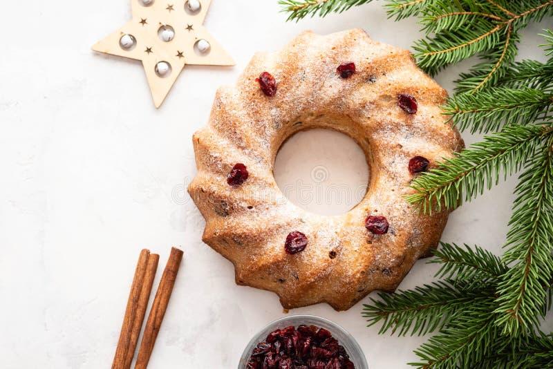 Sobremesa caseiro tradicional do feriado do bolo do Natal com o arando no quadro das decorações da árvore do ano novo no branco d foto de stock