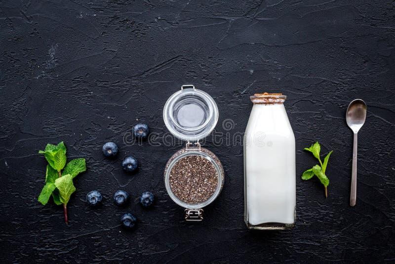Sobremesa clara com sementes, iogurte, mirtilo e hortelã do chia Copyspace preto da opinião superior do fundo foto de stock