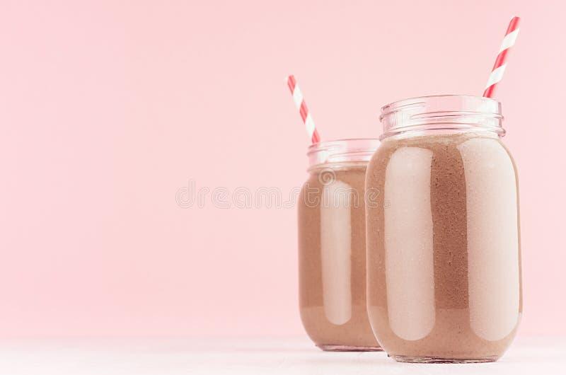 Sobremesa clara excelente do chocolate de leite em uns frascos com palha vermelha no fundo cor-de-rosa elegante moderno da cor imagens de stock royalty free