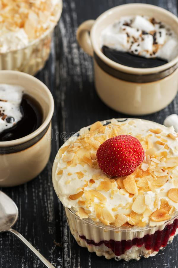 Sobremesa com creme, amêndoas e morangos em uma tabela de madeira, duas xícaras de café com marshmallows Foco seletivo fotografia de stock royalty free