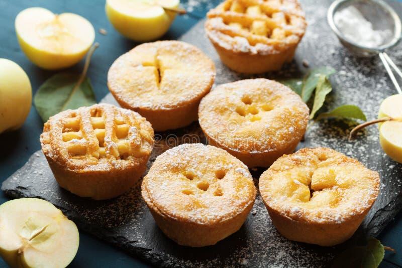 A sobremesa da pastelaria das mini tortas de maçã decorou o pó do açúcar na placa preta da ardósia foto de stock