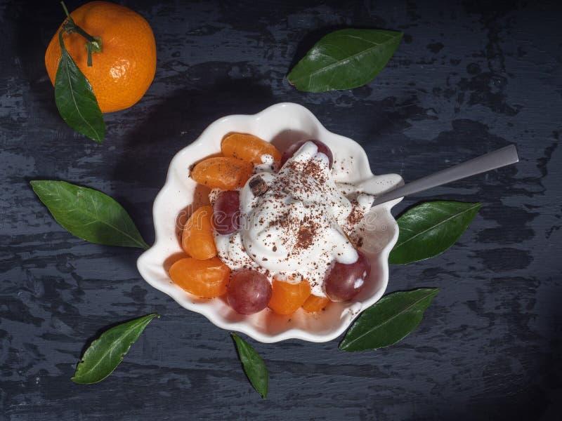 Sobremesa da tangerina e das uvas com chantiliy e chocolate raspado fotografia de stock royalty free