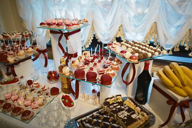 A sobremesa da variedade do casamento endurece com cor saboroso do bufete decorada com creme vermelho chicoteado da pérola, barra foto de stock royalty free