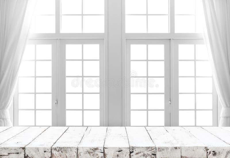 Sobremesa de madera blanca en la falta de definición de la ventana blanca con la cortina imagen de archivo