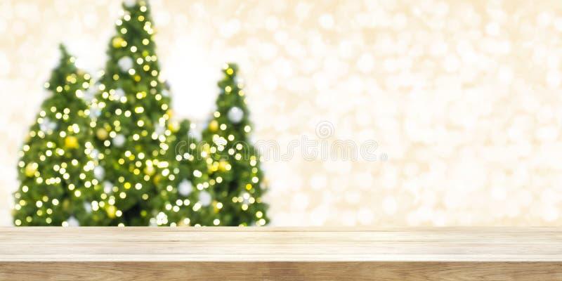 Sobremesa de madera con el árbol de navidad de la falta de definición y el backg de oro del bokeh fotografía de archivo libre de regalías
