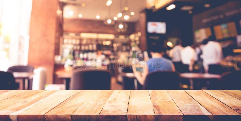 Sobremesa de madera con la cafetería de la falta de definición, fondo del café fotos de archivo libres de regalías
