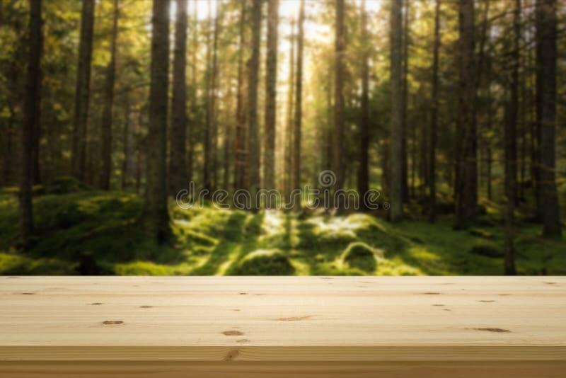 Sobremesa de madera delante del bosque blured verde para el montaje de la exhibición del producto foto de archivo libre de regalías