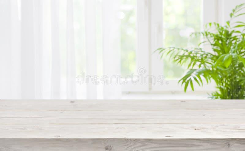 Sobremesa de madera en el fondo borroso de la ventana con la cortina fotos de archivo