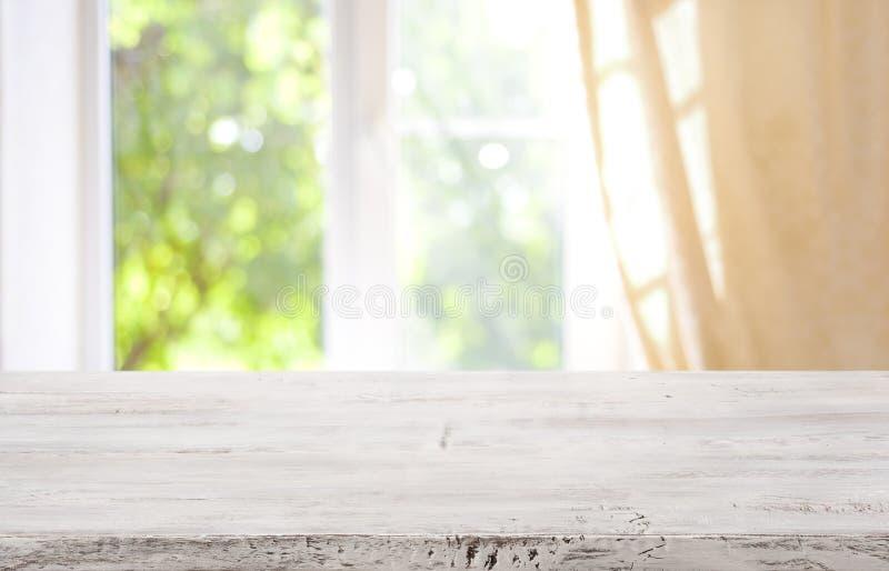 Sobremesa de madera en el fondo borroso de la ventana para la exhibición del producto fotografía de archivo