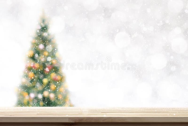 Sobremesa de madera en fondo del árbol de navidad de la falta de definición en nevadas imágenes de archivo libres de regalías