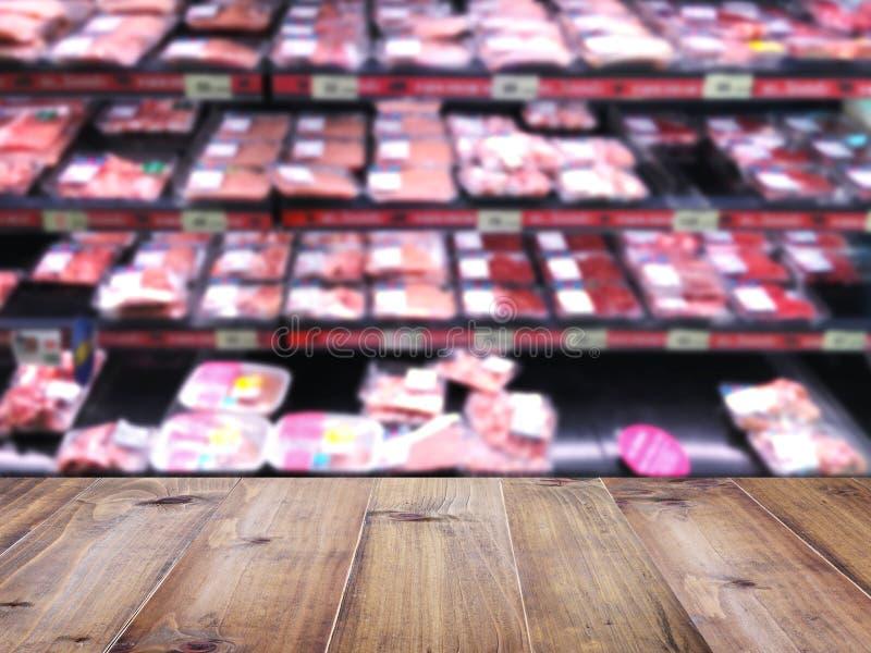 Sobremesa de madera sobre el fondo de la falta de definición del supermercado con la carne favorable fotos de archivo