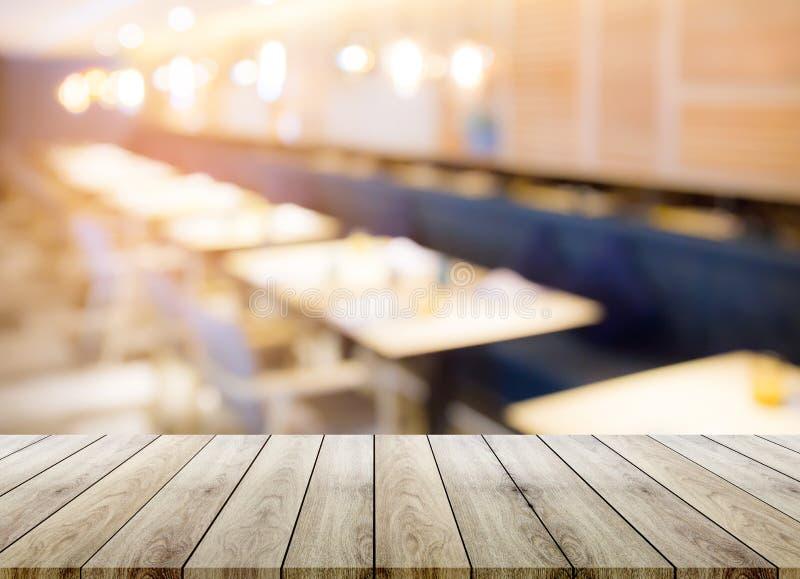 Sobremesa de madera vacía con el fondo del bokeh de la falta de definición del restaurante imágenes de archivo libres de regalías