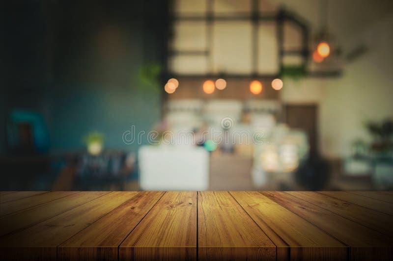 Sobremesa de madera vacía con la cafetería o el restaurante borrosa adentro imagenes de archivo