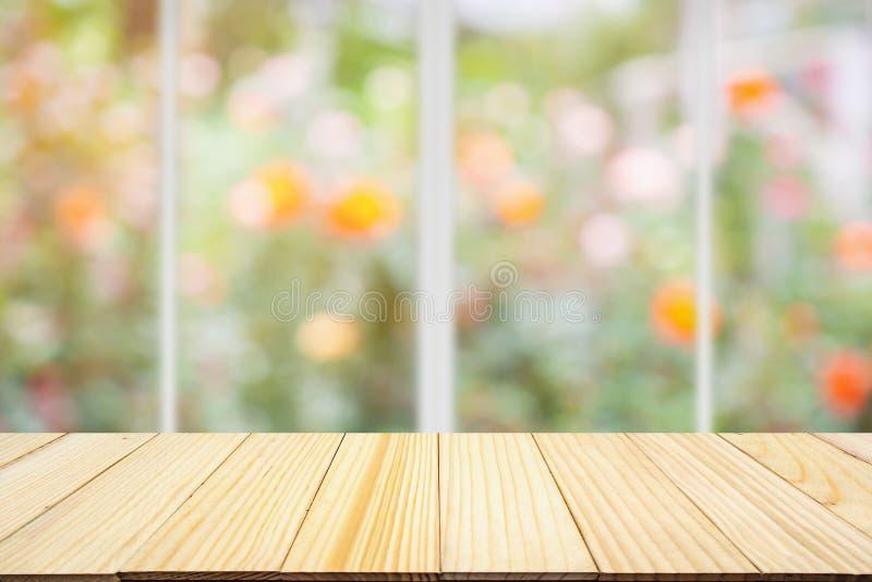 Sobremesa de madera vacía con las flores color de rosa coloridas de la falta de definición del extracto de la ventana de la cocin foto de archivo libre de regalías