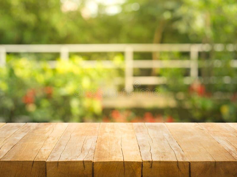 Sobremesa de madera vacía en fondo del jardín y de la casa del extracto de la falta de definición fotografía de archivo