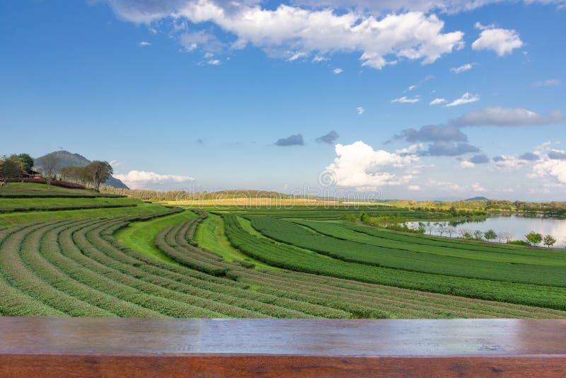 Sobremesa de madera vacía en la opinión del paisaje de la plantación de té con el cielo azul por la tarde, fondo de la naturaleza foto de archivo