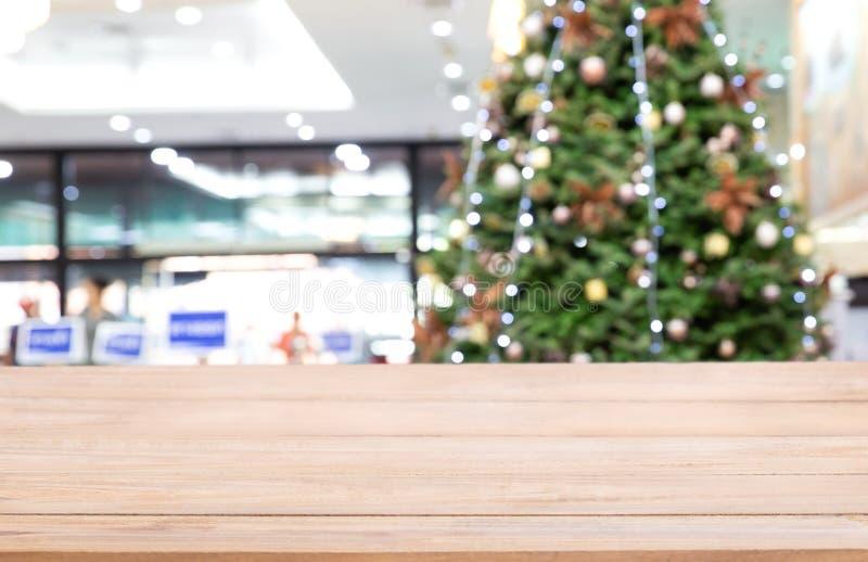 Sobremesa de madera vacía sobre Defocused del árbol de navidad adornado con los juguetes, caja de regalo, luces, chuchería dentro fotos de archivo libres de regalías