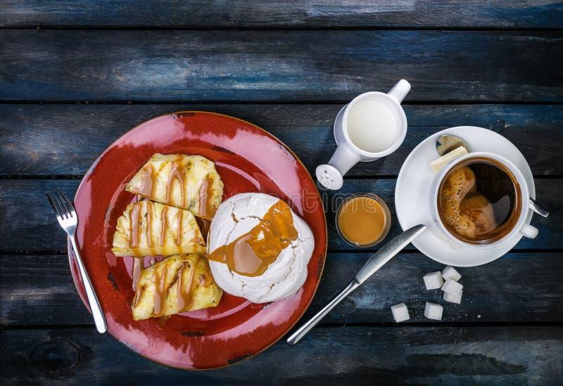 Sobremesa deliciosa Merengue com abacaxi e café fresco em um fundo de madeira colorido Vista superior imagens de stock