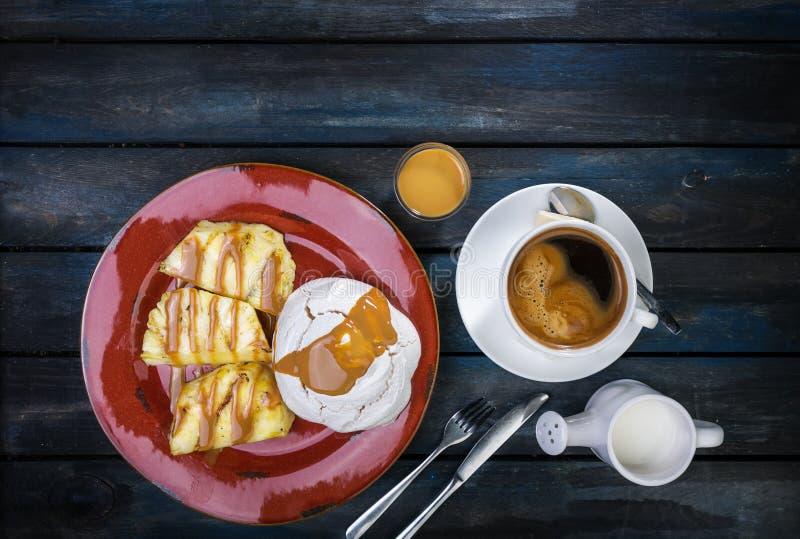 Sobremesa deliciosa Merengue com abacaxi e café fresco em um fundo de madeira colorido Vista superior fotografia de stock