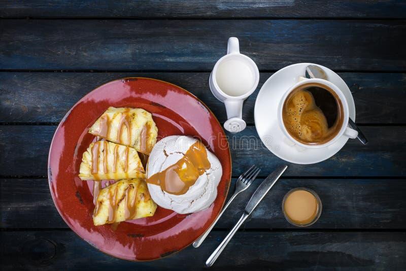 Sobremesa deliciosa Merengue com abacaxi e café e leite frescos em um fundo de madeira colorido Vista superior imagens de stock royalty free