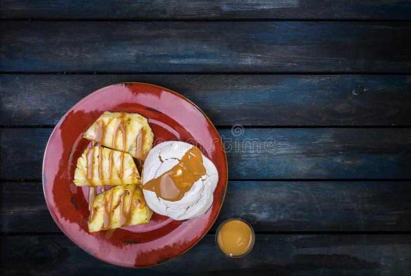 Sobremesa deliciosa Merengue com abacaxi e leite condensado abrandado em um fundo de madeira colorido Vista superior fotos de stock