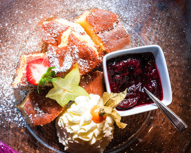 Sobremesa do austríaco típico ou da panqueca alemão com bagas e chicote fotos de stock