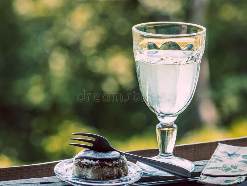 Sobremesa do chocolate do bolo do biscoito com coco e bebida, um vidro da limonada do limão pela janela fotografia de stock