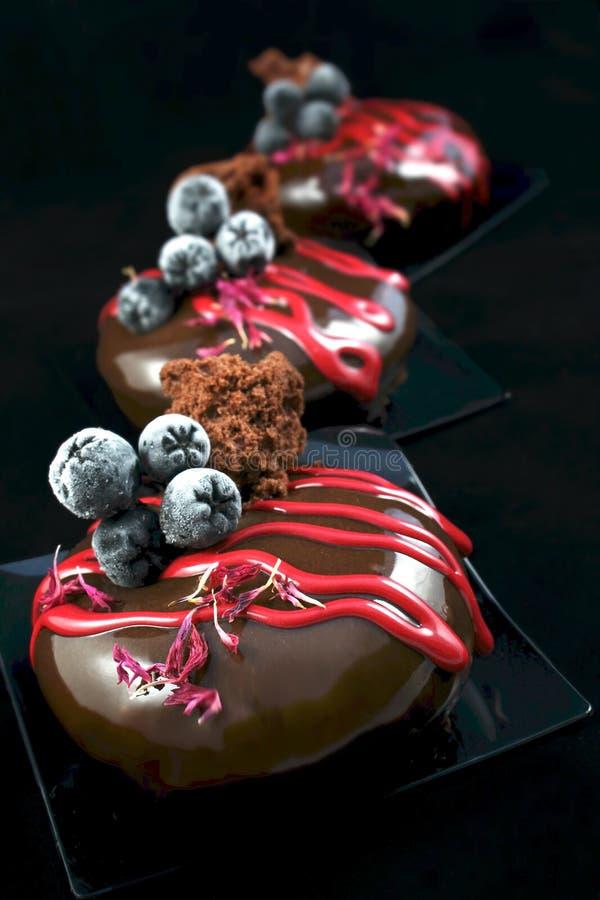 Sobremesa do chocolate com as bagas congeladas do aronia e a decoração vermelha do knapweed imagem de stock royalty free