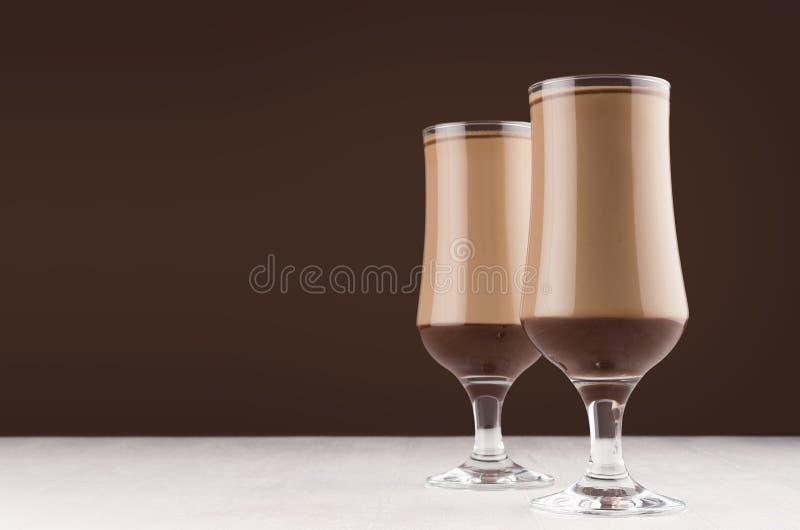 Sobremesa do chocolate e do café em dois vidros transparentes elegantes no interior marrom escuro moderno da cozinha, espaço da c imagens de stock