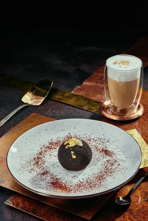 Sobremesa do chocolate sob a forma de uma bola, decorada com folha de ouro em uma placa branca em um fundo das placas de cobre fotografia de stock royalty free