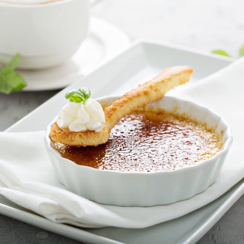 Sobremesa do creme brulée com um copo do cappuccino imagem de stock