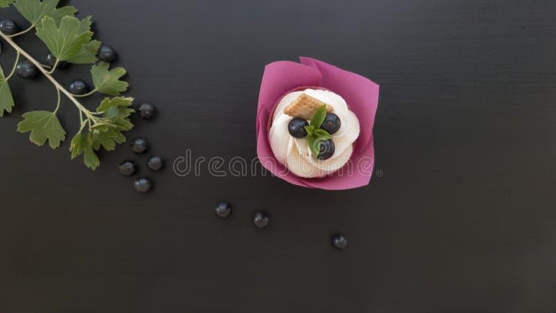Sobremesa do queque em uma tabela preta com folhas e empacotamento roxo foto de stock royalty free