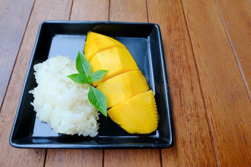 Sobremesa famosa tailandesa: Manga com cobertura do arroz pegajoso com leite de coco foto de stock