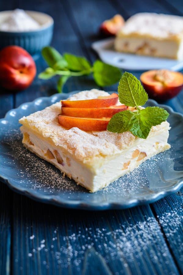 A sobremesa feita de duas camadas da massa folhada encheu-se com o creme e a nectarina do mascarpone imagem de stock