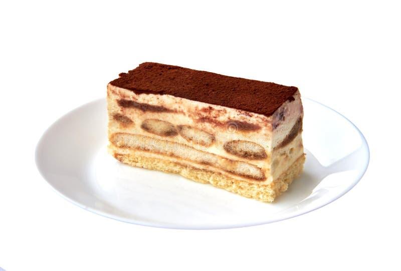 Sobremesa italiana tradicional do bolo do Tiramisu com cacau em uma placa da porcelana no fundo branco Fim acima foto de stock royalty free